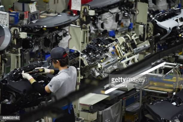 Worker assemble a dashboard on the Prius hybrid and Priyus plug-in hybrid vehicle production line of the Toyota Motor Corp. Tsutsumi plant in Toyota...