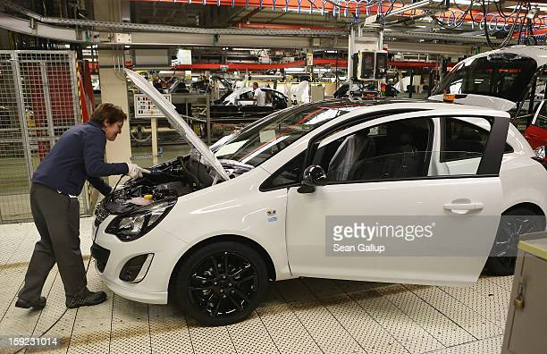 Worker assemble an Opel Corsa car at the Corsa and Adam assembly line at the Opel factory on January 10 2013 in Eisenach Germany Opel employees hope...