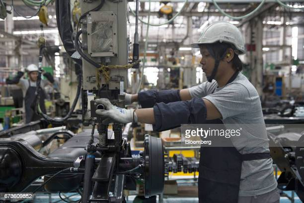 A worker assembles a chassis of a Nissan Motor Co Navara pickup truck on an assembly line at the company's plant in Samut Prakan Thailand on Tuesday...