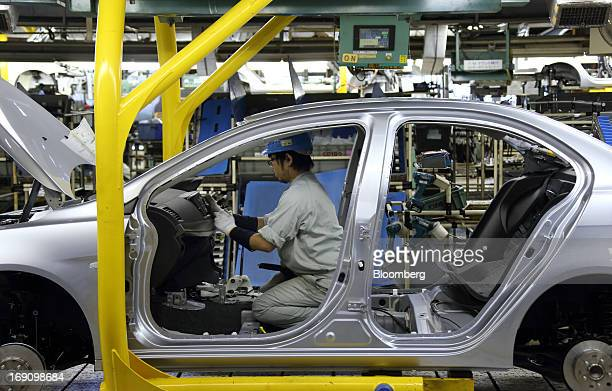 A worker assembles a Mitsubishi Motors Corp vehicle on the production line of the Mitsubishi Motors Mizushima plant in Kurashiki Okayama Prefecture...