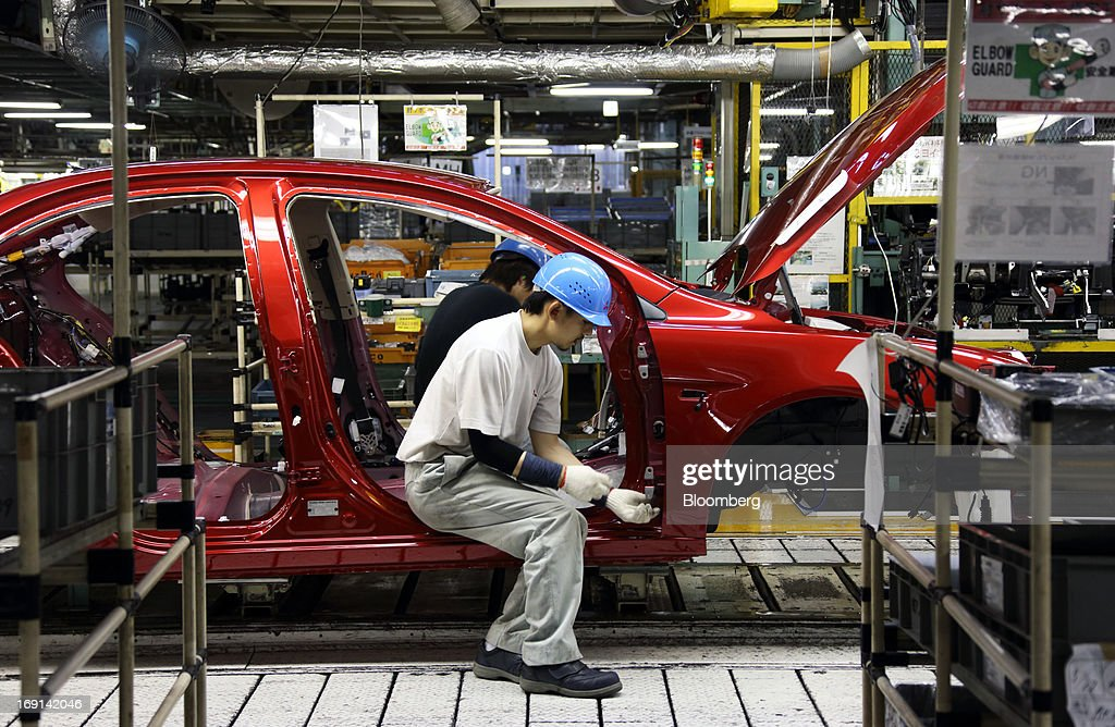 A worker assembles a Mitsubishi Motors Corp. vehicle on the production line of the Mitsubishi Motors Mizushima plant in Kurashiki City, Okayama Prefecture, Japan, on Monday, May 20, 2013. Nissan will start selling the first minicar it jointly developed with Mitsubishi Motors in Japan next month amid increasing demand from the nation's consumers for smaller and cheaper vehicles. Photographer: Tomohiro Ohsumi/Bloomberg via Getty Images