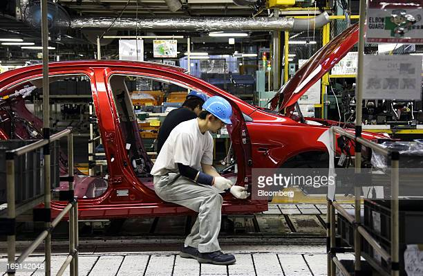 A worker assembles a Mitsubishi Motors Corp vehicle on the production line of the Mitsubishi Motors Mizushima plant in Kurashiki City Okayama...