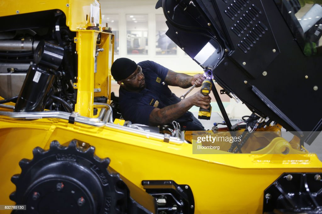 A worker assembles a skid steer loader construction vehicle at the JC Bamford Excavators LTD. (JCB) manufacturing plant in Pooler, Georgia, U.S., on Friday, Aug. 11, 2017. The Federal Reserve is scheduled to release industrial production figures on August 17. Photographer: Luke Sharrett/Bloomberg via Getty Images