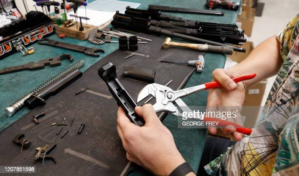 A worker assembles a trigger assembly on an AR15 rifle at Delta Team Tactical in Orem Utah on March 20 2020 Gun stores in the US are reporting a...