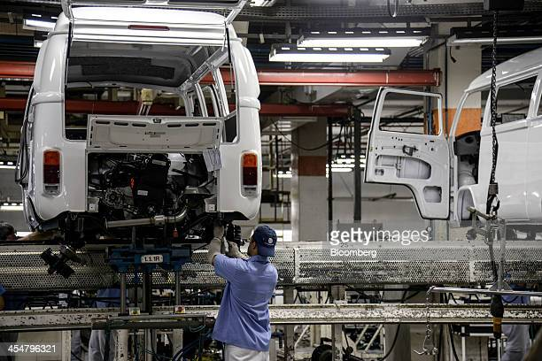 A worker assembles a Volkswagen AG camper van or microbus known as a 'Kombi' in Brazil on the production line at Volkswagen's Anchieta plant in Sao...