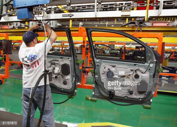 A worker assembles car door units at Ford's Chicago Assembly Plant August 10 2004 in Chicago Illinois Ford previewed to the news media the Chicago...