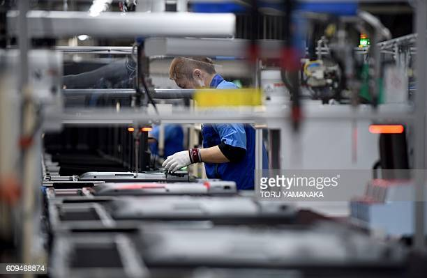 A worker assembles LCD 4K televisions on an assembly line at the Utsunomiya Plant of Japan's electronics giant Panasonic in Utsunomiya 100 kilometres...