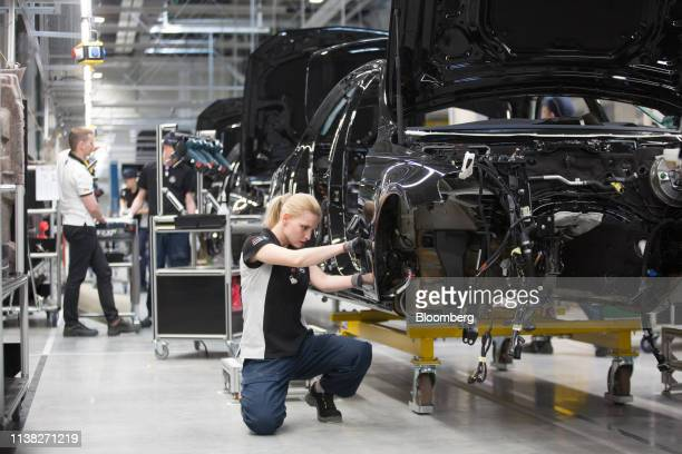 A worker assembles MercedesBenz EClass automobiles on the production line at the Daimler AG luxury automobile plant in Moscow Russia on Friday April...