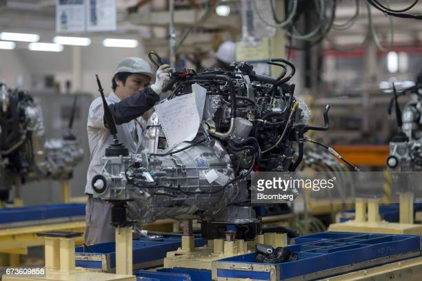 A worker assembles the engine of a Nissan Motor Co Navara pickup truck on an assembly line at the company's plant in Samut Prakan Thailand on Tuesday...