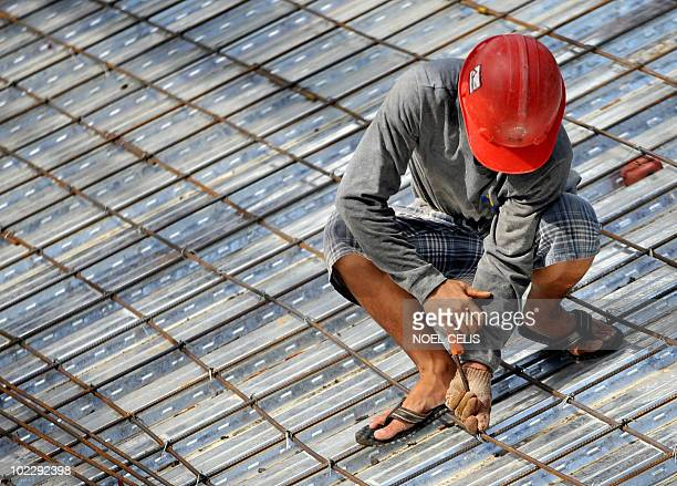 A worker assembles the metal frame of an elementary school under construction in Manila on June 21 2010 The Philippines' jobless rate rose to a near...