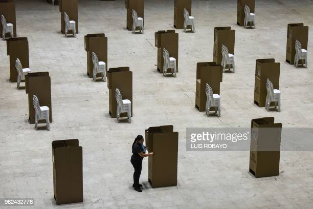 TOPSHOT A worker assembles voting booths at a polling station in Cali Colombia on May 25 2018 Colombia will hold the first round of the presidential...
