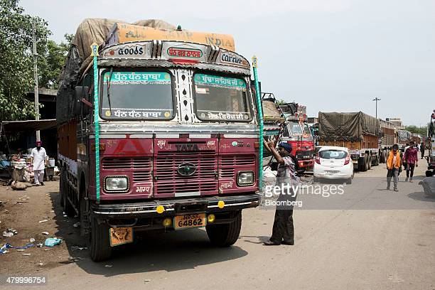 A worker assists in directing a truck outside the Caravan Roadways Ltd office at Sanjay Gandhi Transport Nagar in Delhi India on Monday June 22 2015...