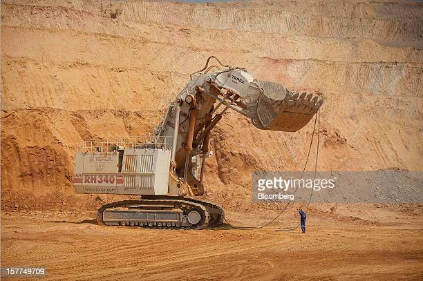 A worker assists in the operation of a giant Terex Corp mining excavator during the extraction of ore from the open pit at Katanga Mining Ltd's KOV...