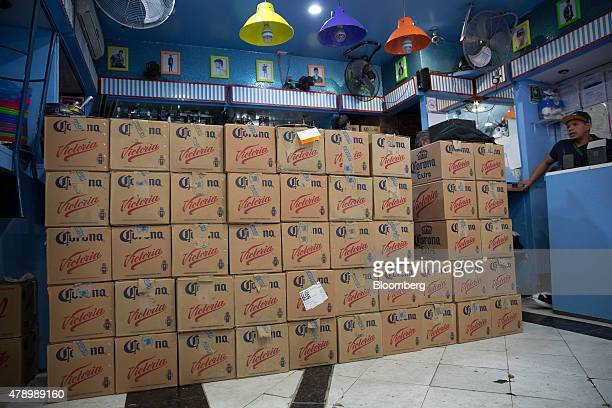 A worker at a bar looks on as cases of Constellation Brands Inc Corona and Victoria beer are delivered in the Zona Rosa neighborhood in Mexico City...