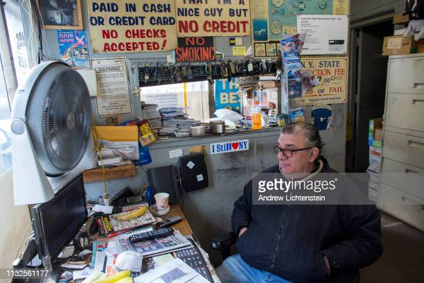 A worker at a car repair shop in watches President Trump's former lawyer Michael Cohen testify on television to Congress on February 27 2019 in...