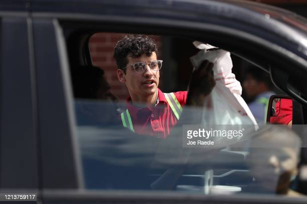 A worker at a ChickfilA delivers a meal to customers in their vehicles at the driveup window after the restaurant closed its indoor seating in an...
