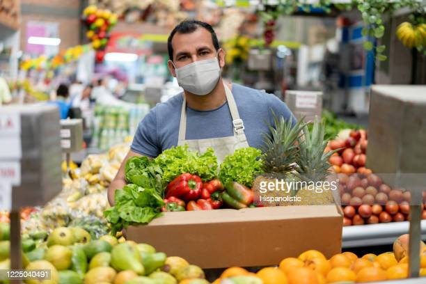 worker at a food market restocking the shelves and wearing a facemask - agricultural fair stock pictures, royalty-free photos & images