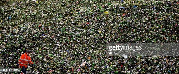 A worker at a glass recycling center walks past a large pile of glass bottles on January 2 2014 in Gameren The Netherlands Trucks are constantly...