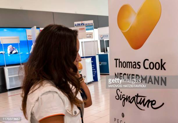 A worker at a travel agency which partners of Thomas Cook speaks on the phone at the Larnaca International Airport in the Cypriot coastal city on...