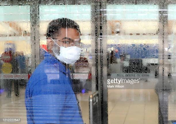 Worker at Baltimore/Washington International Thurgood Marshall Airport wears a mask as he cleans a glass door as concerns for the coronavirus grow,...
