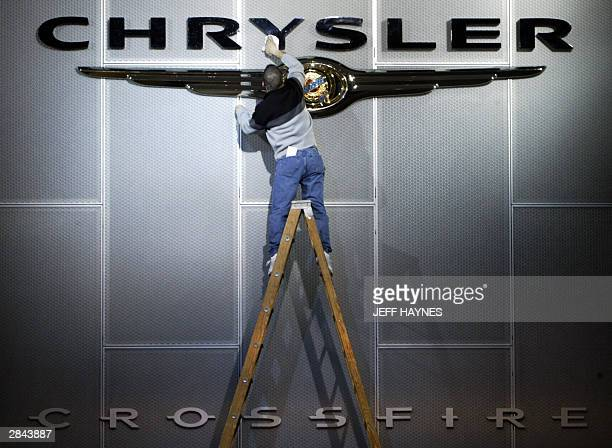 A worker at Cobo Hall polishes the sign at the Chrysler display 04 January 2004 during press day at the North American International Auto Show at...