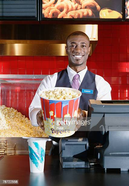 Worker at Concession Counter Handing over Bucket of Popcorn
