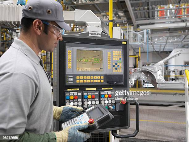 Worker At Controls In Car Plant