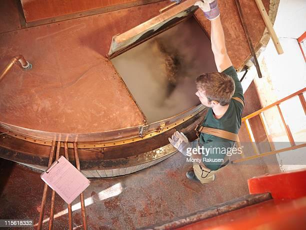 worker at copper tank in brewery - tanque de armazenamento imagens e fotografias de stock
