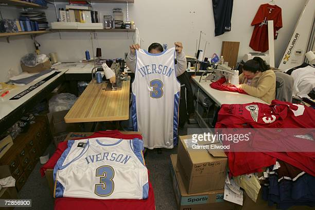 A worker at Denver Athletic holds up the official game jersey for newly acquired player Allen Iverson of the Denver Nuggets on December 20 2006 in...