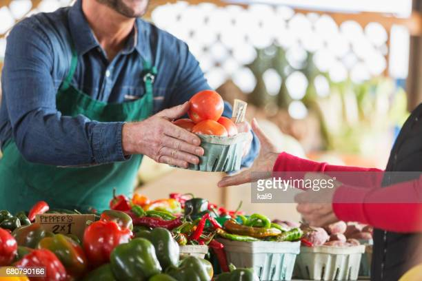 worker at farmer's market selling tomatoes to customer - farmers market stock pictures, royalty-free photos & images
