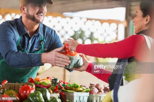 Arbeiter am Bauernmarkt Tomaten an Kunden zu verkaufen