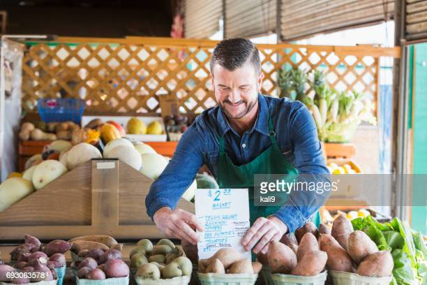 worker at farmer's market setting up display, price sign - farm to table stock photos and pictures