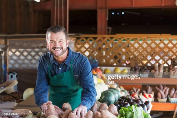 worker at farmer's market setting up produce stand - bancarella di verdura foto e immagini stock