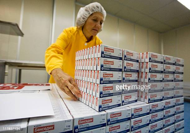 A worker at Galenika a major Serbian pharmaceutical company stacks on October 23 2009 packages of Bensedin antidepressant pills A Benjo a day takes...