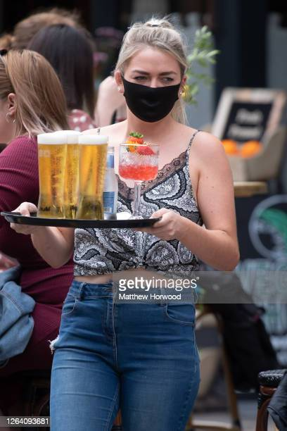 A worker at Gin and Juice gin bar wears a face mask as she serves drinks on August 5 2020 in Cardiff United Kingdom Coronavirus lockdown measures...