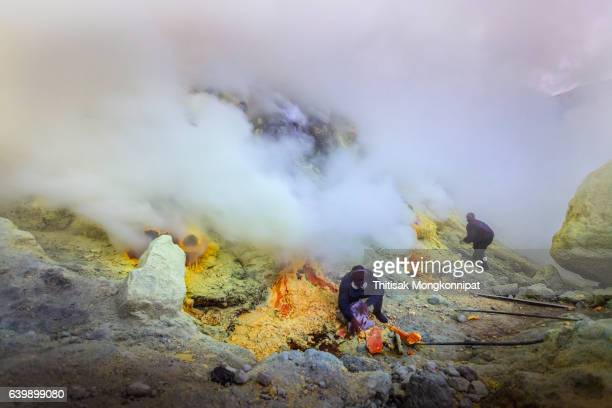 worker at ijen sulfur mining - acid warning stock photos and pictures
