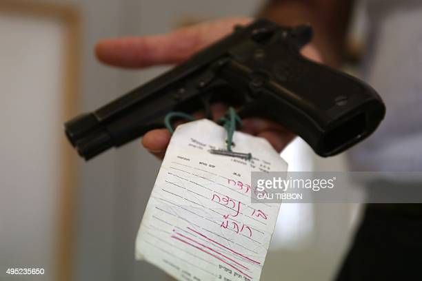 A worker at Israel's National archives displays the 9mm Berreta pistol that was used in the assassination of late prime minister Yitzhak Rabin 20...