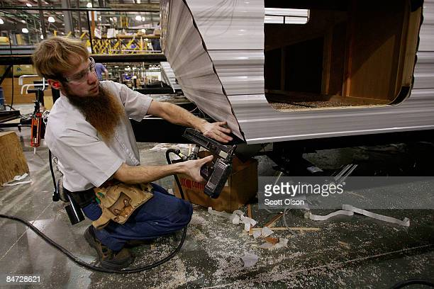 A worker at Jayco Inc the country's third largest maker of recreational vehicles puts siding on a Jay Flight travel trailer February 10 2009 in...