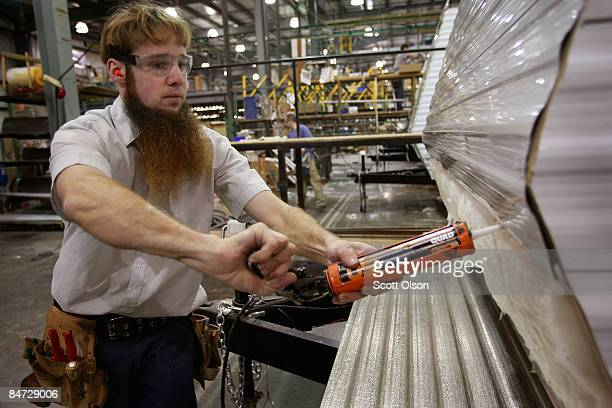 A worker at Jayco Inc the country's third largest maker of recreational vehicles prepares to put siding on a Jay Flight travel trailer February 10...