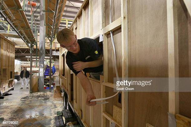 A worker at Jayco Inc the country's third largest maker of recreational vehicles runs electrical cable during the construction of a Jay Flight travel...