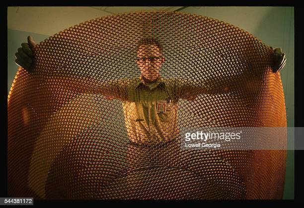 A worker at Martin Marietta Labs holds a piece of mesh material that will be used as a heat shield for the Mars Viking lander The shield is designed...