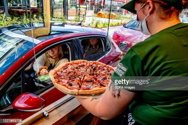 Worker at New York Pizza wearing a mask serves pizza to a customer through her car at the Pizza drive-thru. New York Pizza opens the first Pizza...