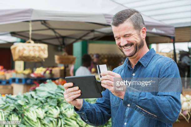 worker at produce market processing credit card - credit card reader stock pictures, royalty-free photos & images