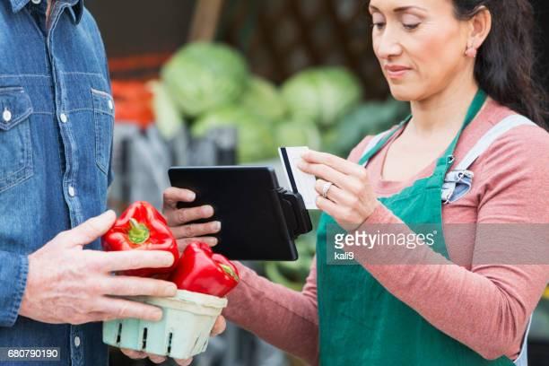 Werknemer op produceren markt verwerking creditcard
