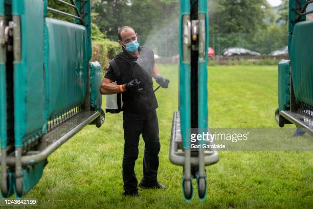 Worker at San Sebastian Hippodrome wearing a face mask disinfects the stalls during the first race of the season in the San Sebastian Hippodrome on...