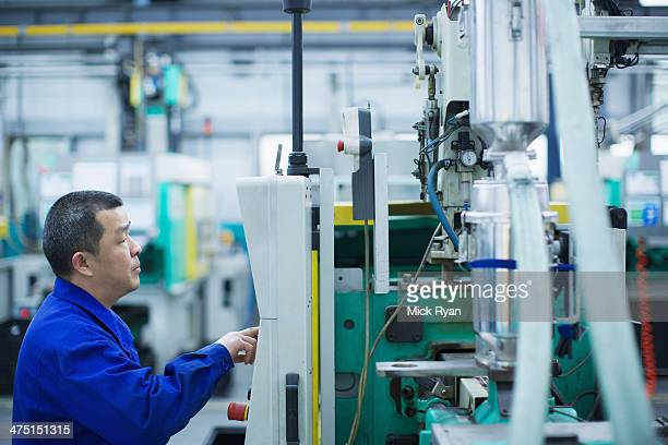 Worker at small parts manufacturing factory in China, pressing button on control panel