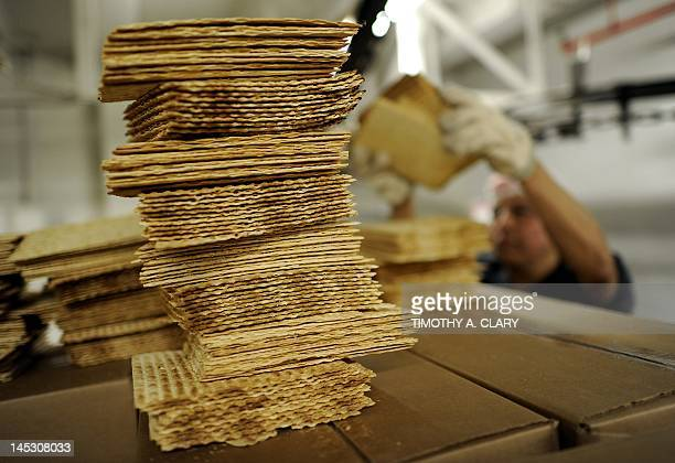 A worker at Streit's Matzo factory on the lower east side of New York stacks matzo wafers on May 9 2012 Aron Streit Inc is a kosher food company...