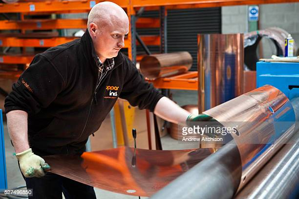 A worker at the Copper Industries factory in Northern Ireland bends copper sheeting for the manufacture of hot water tanks for use with the Willis...