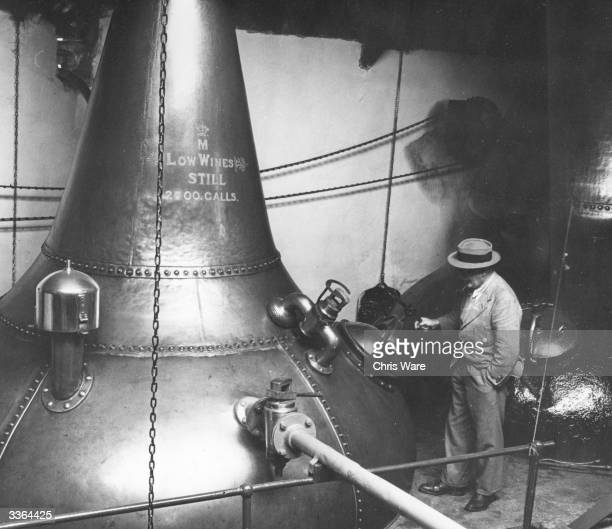 A worker at the Glen Mohr whisky distillery in Inverness inspecting one of the copper stills where alcohol is extracted from waste grain pulp...