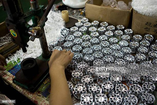 A worker at the Guangdong Qunxing Toys Industrial Co Ltd works with wheels for a remote controlled toy car in the Chenghai district of Shantou...